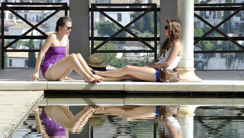 Dos jóvenes descansan junto al agua