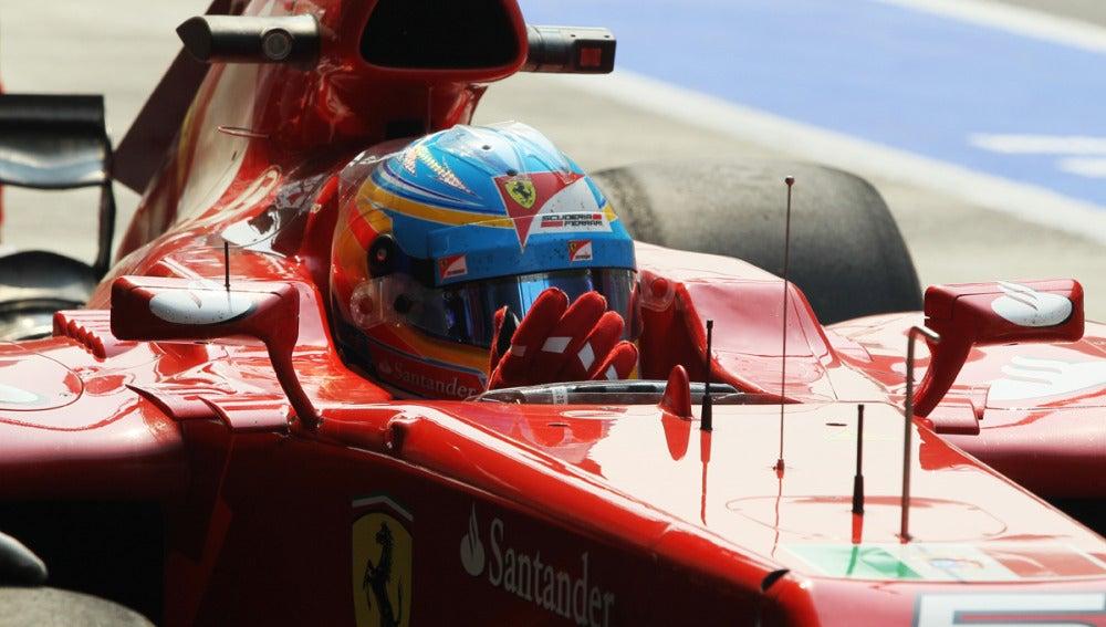 Alonso, subido en su Ferrari