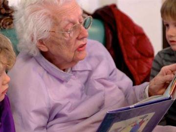 Una anciana leyéndole un cuento a dos niños