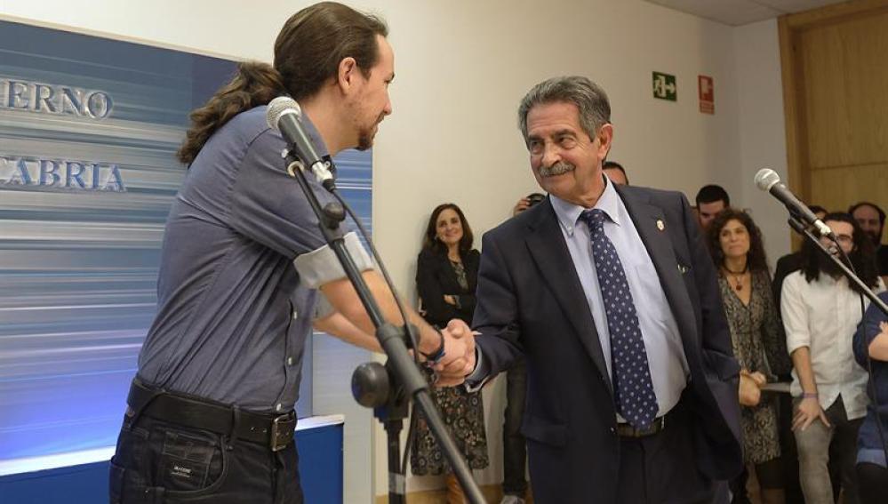 Pablo Iglesias y Miguel Ángel Revilla se saludan durante una rueda de prensa