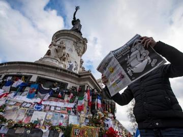 Un hombre lee la revista Charlie Hebdo frente al homenaje a las víctimas