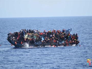 Dramática imagen de una barcaza de inmigrantes volcando en el mar