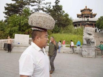 Cong Yan caminando con una piedra en la cabeza