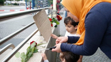 Una mujer enciende velas con dos niños en honor a las víctimas