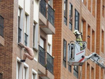 Un hombre desnudo se descuelga por un edificio