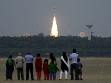 Gente mirando el lanzamiento de un cohete en la India