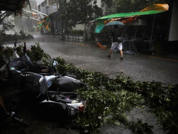 Un hombre camina por la calle frente a unas motocicletas desplazadas por el tifón Megi en Hualien, Taiwan