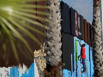 Un voluntario pinta murales en la cerca que marca el límite en la frontera entre EEUU y México