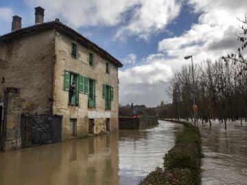 Una mujer observa desde su casa el desbordamiento del río Arga
