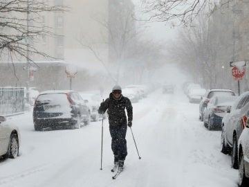 Un hombre caminando con esquís por la calle en Brooklyn