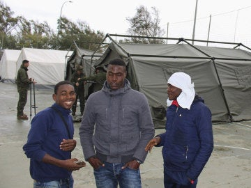 Un grupo de inmigrantes al lado de una tienda de campaña