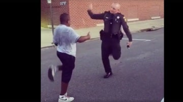 Un agente de policía baila con un adolescente