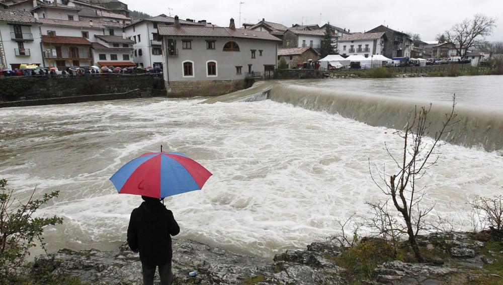 Una persona observa la crecida del río Esca en Navarra