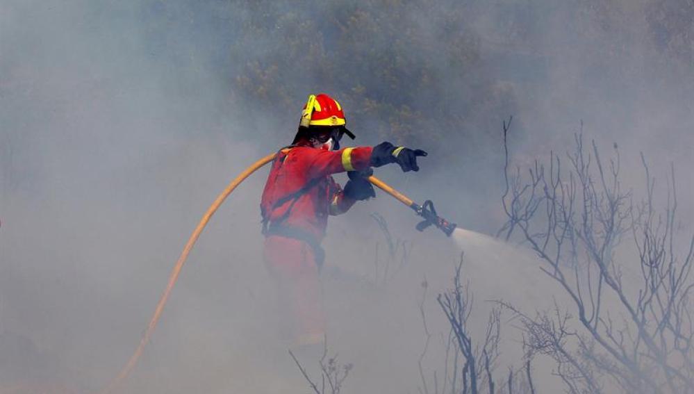 Un bombero intenta apagar el fuego en Valencia