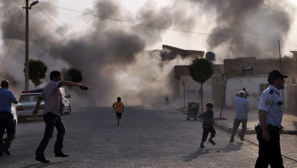 Unos ciudadanos turcos escapan del humo provocado por el estallido de una bomba de mortero lanzada en Sanliurfa