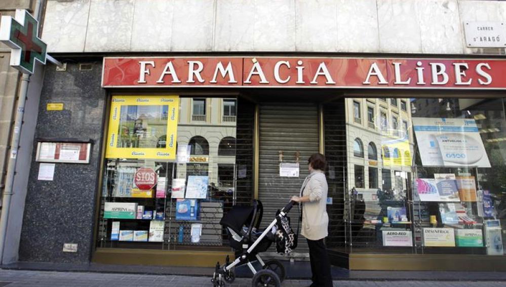 Una mujer contempla la fachada de una farmacia cerrada en el centro de Barcelona