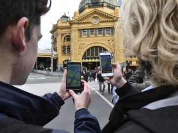 Dos estudiantes prueban el nuevo juego 'Pokémon Go' en su móvil