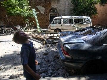 Un niño camina junto a vehículos y edificaciones dañados por un ataque aéreo