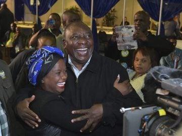 El vicepresidente sudafricano, Cyril Ramaphosa (c), abrazando a una de sus votantes a su llegada a la sede de su partido