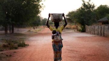 Mujer cargando con un cubo de agua