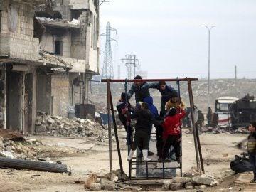 Niños sirios juegan entre las ruinas de una ciudad arrasada por la guerra