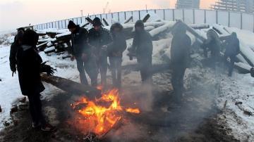 Varios refugiados se protegen del frío con una hoguera