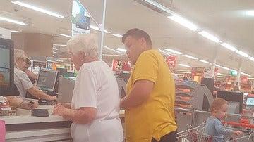 Momento en el que el hombre paga la compra a la anciana