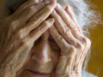 Una mujer tapándose la cara con las manos