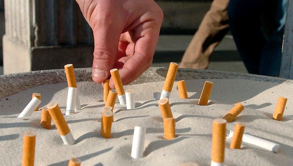 Un hombre apaga un cigarrillo en un cenicero