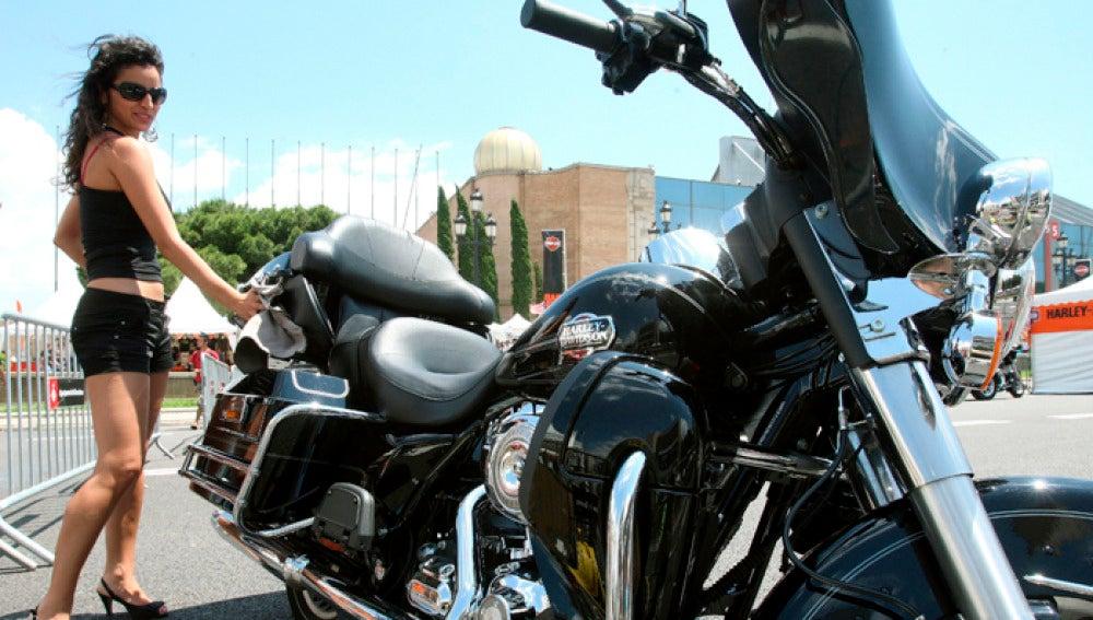 Una joven ante una motocicleta Harley  Davidson