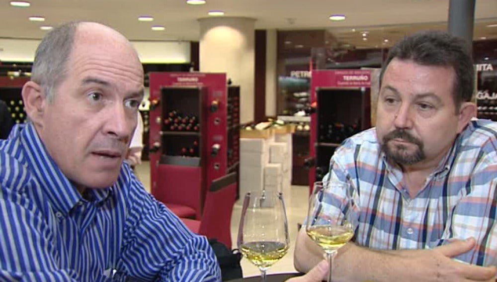 Dos personas bebiendo vino en una bodega