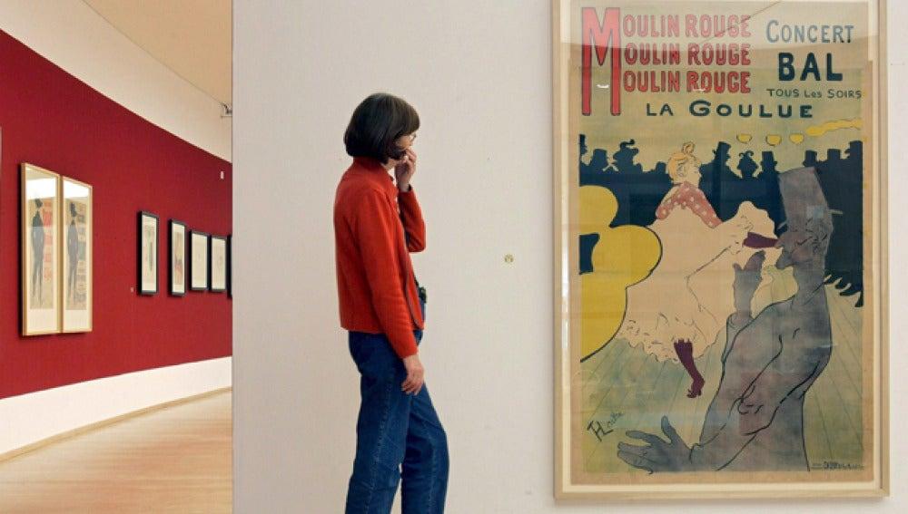 Una mujer contempla la litografía 'Moulin Rouge', de Toulouse-Lautrec