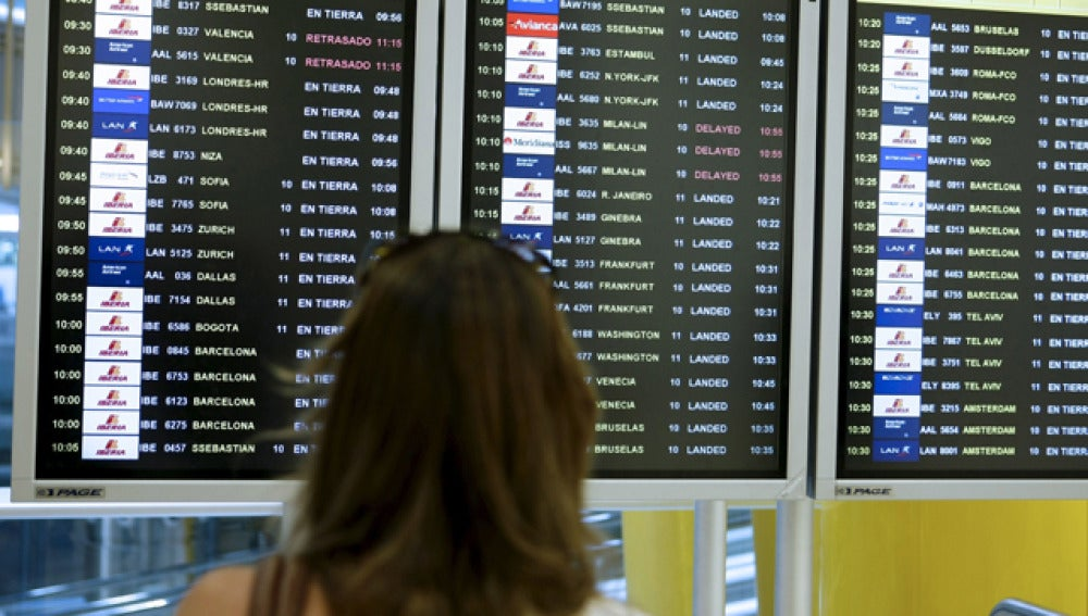 Una mujer observa la pantalla de vuelos en un aeropuerto
