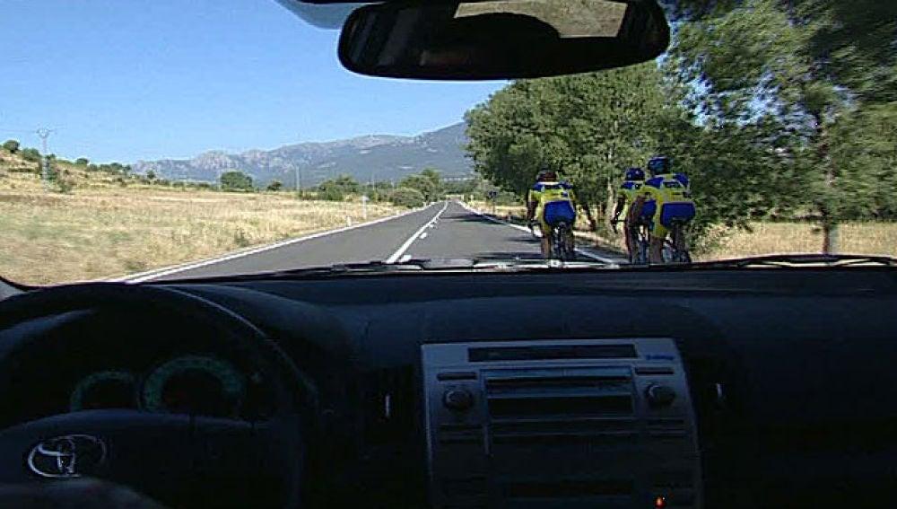 Un coche adelanta un pelotón de ciclistas