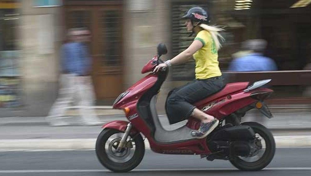 Una joven conduce su ciclomotor