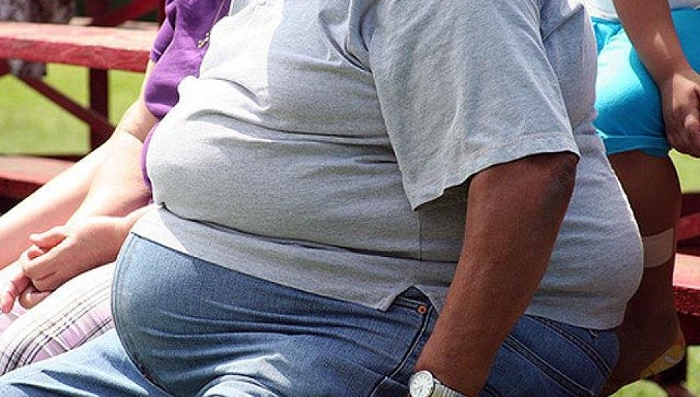Un hombre obeso sentado en un banco