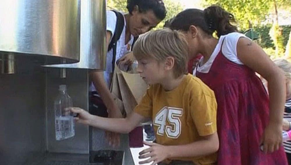 Un niño rellena su botella en la fuente de agua con gas