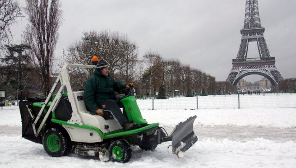 Un operario municipal limpia una calle cubierta de nieve en París