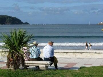 Unos jubilados sentados en un banco frente a la playa