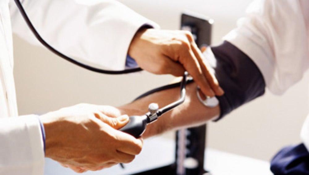 Un médico mide la presión arterial