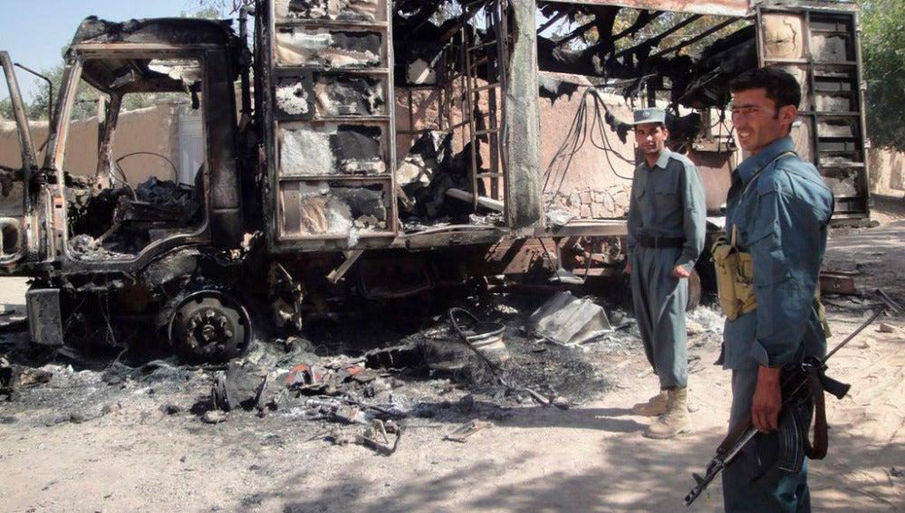 Policías afganos hacen guardia junto a un camión quemado por un grupo de afganos