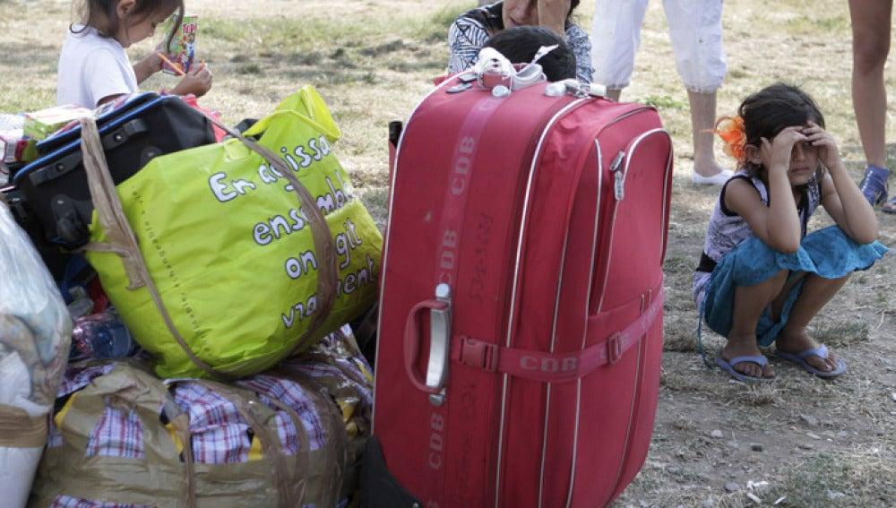 Una familia de rumanos espera tras ser desalojada de su residencia en Francia.