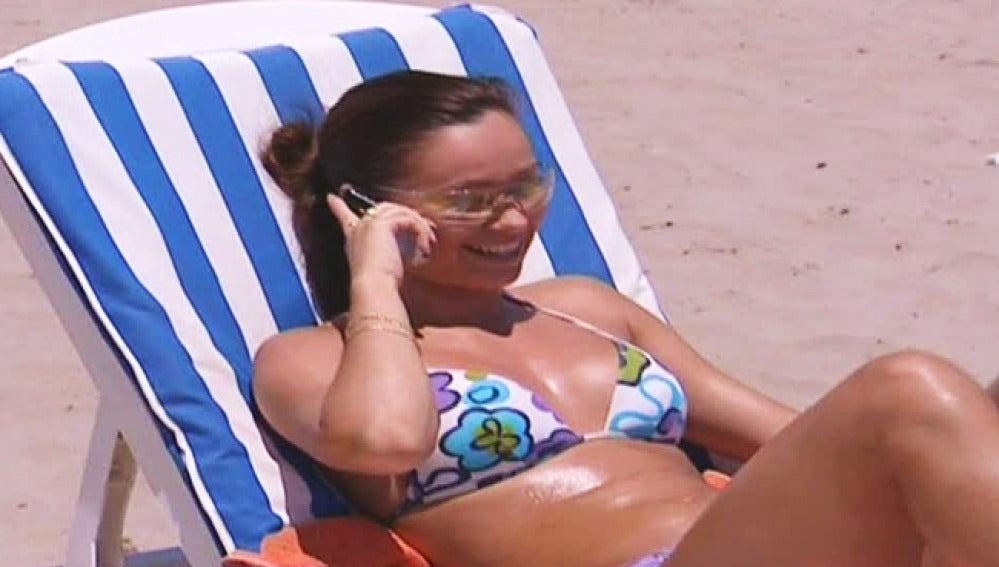 Una joven habla por el móvil en la playa.