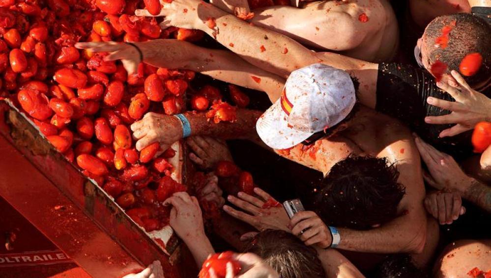Varias personas cogen los tomates que caen del remolque