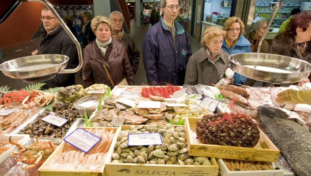 Un grupo de personas hacen cola ante una pescadería en el Mercado de Vitoria