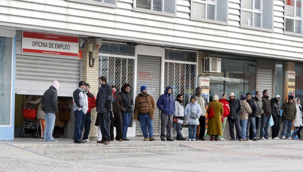 Ciudadanos hacen cola en la puerta de una oficina de empleo