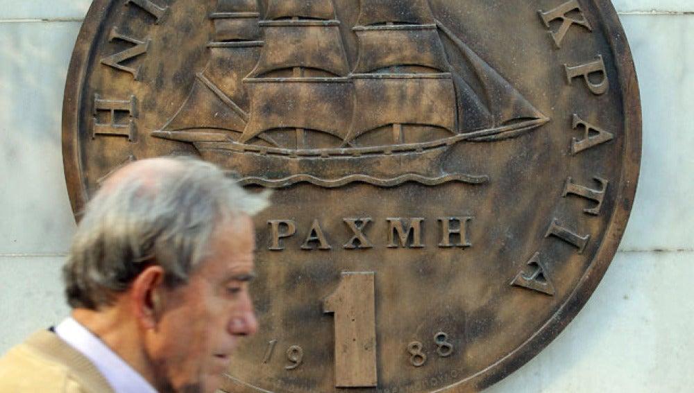 Un hombre camina frente al drachma griego