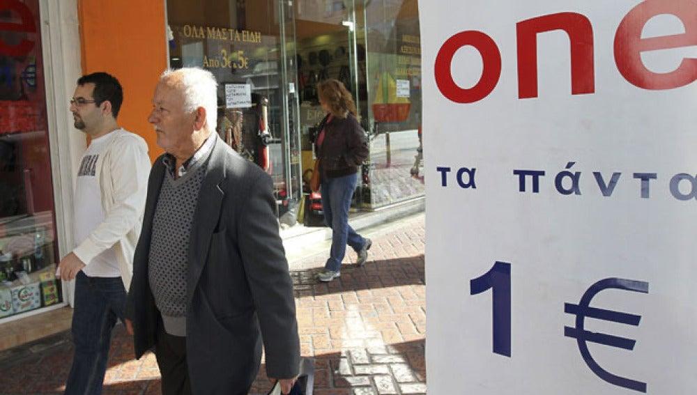 """Unos peatones pasan al lado de una tienda de """"todo a un euro"""" en Atenas"""