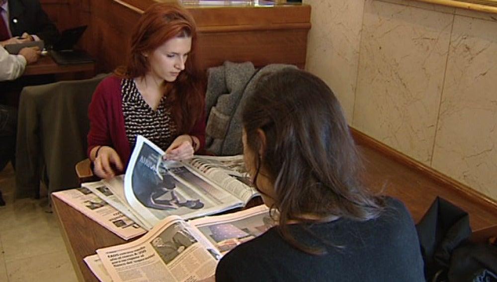 Dos jóvenes leen los diarios económicos