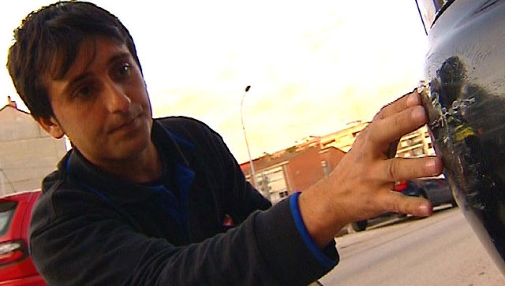 Vicente, un mecánico valenciano, examina un coche